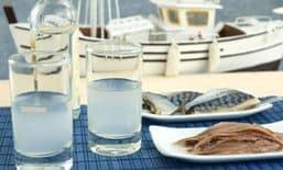 2 ποτήρια με ούζο και πιατάκια με μεζε κοντά στη θάλασσα