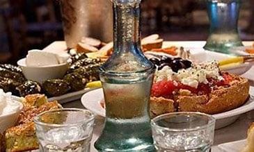 τραπέζι με μεζέδες και ρακι σε μπουκάλι και ποτήρια