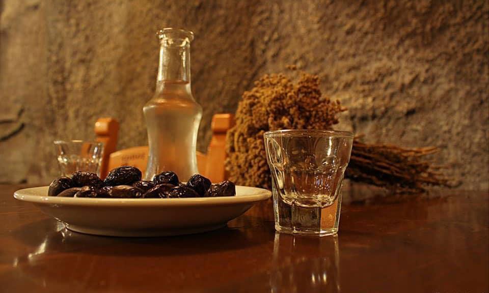 πιάτο με ελιές και ποτήρι και μπουκαλάκι με τσίπουρο